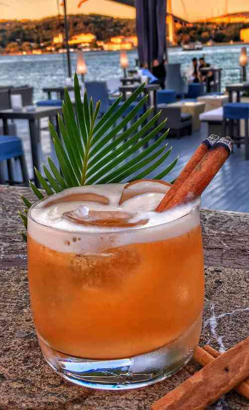 https://cocktailsandshots.com/wp-content/uploads/2018/06/sunset_cocktail_recipe_made_with_gin_amaretto_aperol_passion_fruit_lime_juice_and_a_cinnamon_stick.jpg